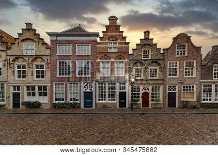 Amsterdam City House With The Typical Flemish Architectural Style Laying In Line Under A Tiny Rain W