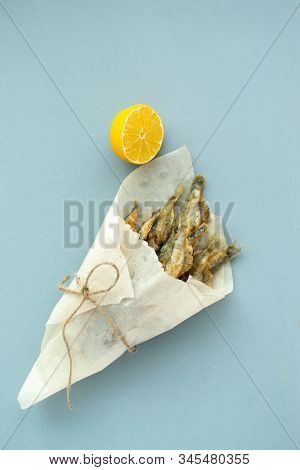 Fried Capelin With Lemon On Baking Paper On A Gray Background. Top View