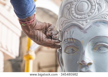 Close Up Of Man Ceramist Hands Holding A Tool And Working On Sculpture Details In Workshop.