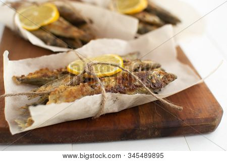 Fried Capelin With Lemon On Baking Paper On A White Background