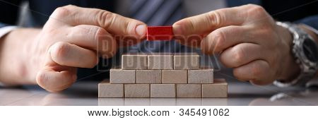Close-up View Of Presentable Man Putting Unique Red Block On Staircase Of Other Identical Bricks. Py