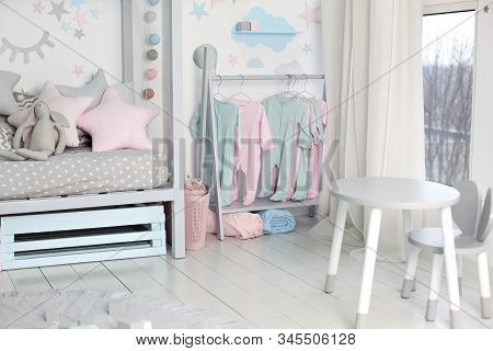 Clothes For Little Child Hung In Children Room. Rack With Hangers With Baby Clothes. Children Cloth