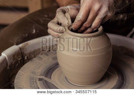 Close-up View On Dirty Man Hands Of Potter Creating With Fingers And Pressure An Earthen Jar Pot Of