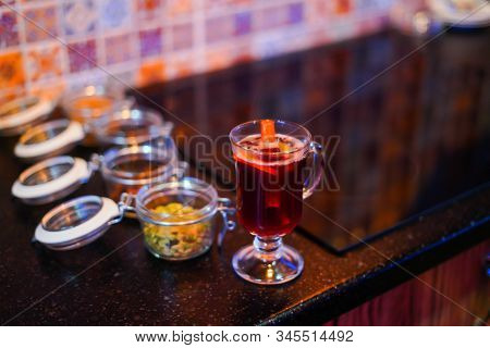 Mulled Wine Preparation, A Glass Of Mulled Wine Is On The Table, Side View Are The Ingredients For M