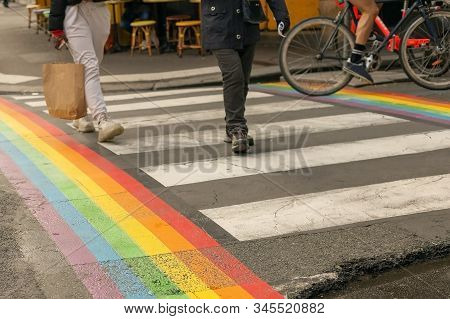 Gay Pride Flag, Rainbow Flag Of The Lgbt Community On Crosswalk With People Crossing In Paris. Lgbt