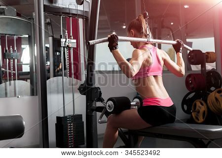 Slim Woman Wearing Pink And Black Professional Sportswear Exercising With An Iron Barbell At The Sun
