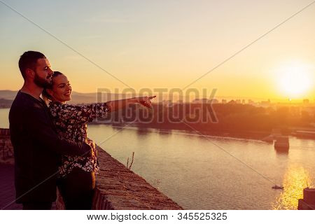 Happy Loving Man And Woman Watching The Sunset