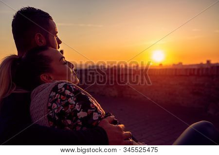 Loving Man And Woman Watching  At Evening The Sunset