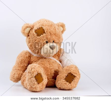 Large Beige Teddy Bear With Patches Sits On A White Background, Left Paw Is Bandaged With A White Me