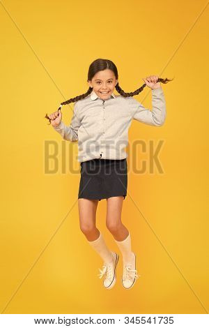 She Is Hyper. Happy Energetic Kid Jumping On Yellow Background. Little Girl With Long Hair Braids Fe