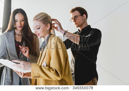 Producer Talking With Model And Hairstylist Doing Hairstyle On Backstage