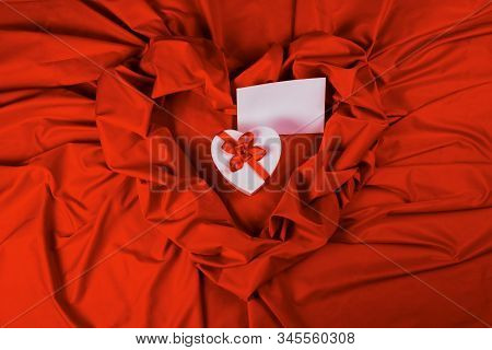 Valentines Greeting Card. White Cardboard Box In Shape Of Heart Wrapped In Ribbon And Blank Paper La