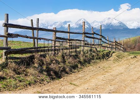 Rural Landscape In Spring. Composite Landscape Of Mountain Ridge In The Distance With Snow Capped To