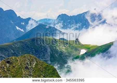 Peaks Of Mountain Ridge Above The Clouds. Gorgeous Scenery Of Romanian Mountains. Fagaras Massif In