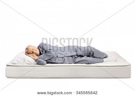Elderly man in pajamas sleeping on a bed mattress isolated on white background
