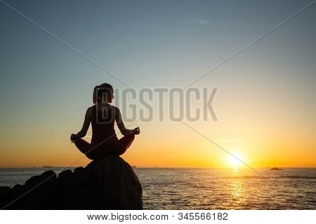 Yoga woman on the ocean coast during warm sunset.