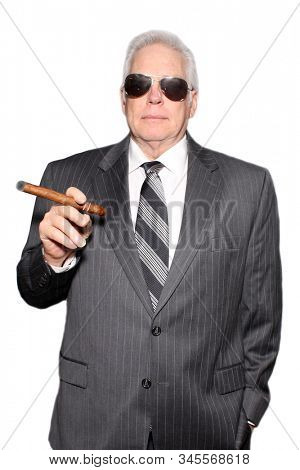 Business man with a Cigar. A business man in a pin striped suit holds and enjoys a fine cigar. Isolated on white. Room for text overlay. People world wide enjoy fine cigars and tobacco products.