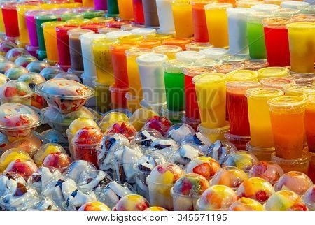 Multicolour Background Of Fresh Smoothie And Fruits Cutted Into Pieces In Plastic Cups, Close Up Vie