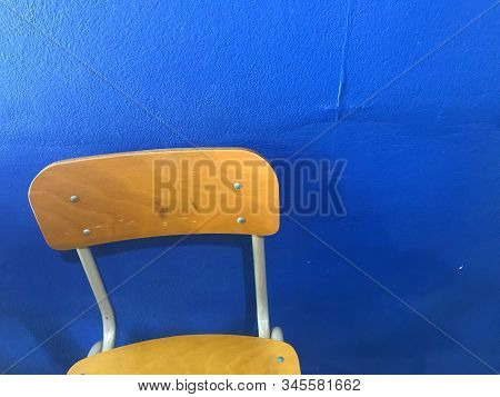 Brown Empty School Chairs With Blue Wall On Background In Natural Daylight, Nostalgia And Alone Conc