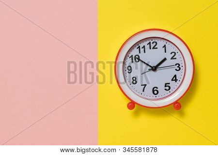 Analog Alarm Clock With Arrows On A Yellow And Pink Background. Classic Analog Clock.