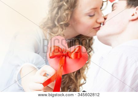 A Young Woman With Curly Hair Holds Red Heart - Valentines Days Card In Her Hands And Kiss With Man.