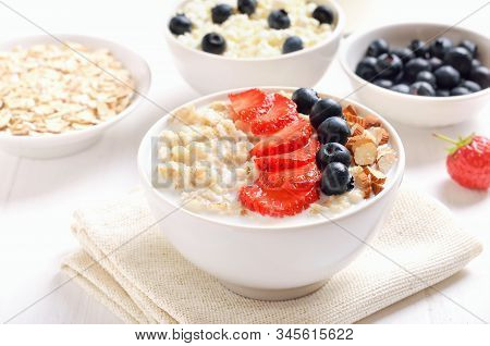 Oatmeal Porridge With Strawberry Slices, Blueberries And Nuts In Bowl On White Table