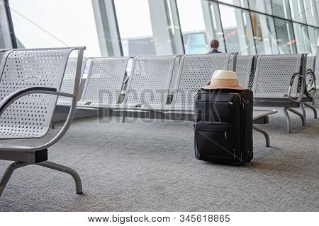 Suitcase In An Airport Waiting Area, One Black Suitcase In An Airport Waiting Room.