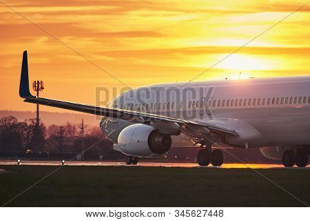 Airplane Before Take Off On Runway. Traffic At Airport Against Sky During Colorful Sunset.