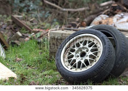Dumped Car Tyres. Fly-tipping Old Tyre Waste And Rubber Recycling. Two Vehicle Tires Discarded Illeg