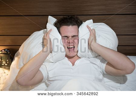 young caucasian man in bad sleeping holding pillow silence noise trying to sleep cry