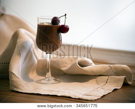Chocolate Mousse, Vanilla Mousse, Chocolate Sauce In A Glass With Two Cherries On The Wooden Table.