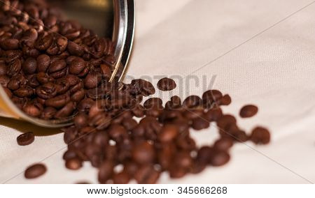 Beans Of Strong Coffee Are Spread Out Of The Tin Can. Morning Drink. Background.