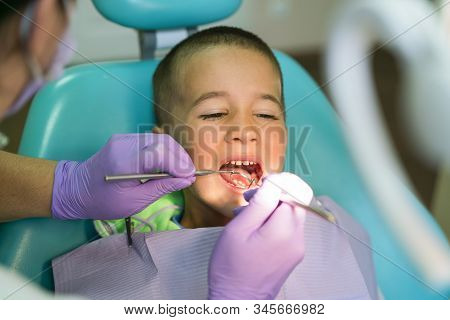 Pediatric Dentist Examining A Little Boys Teeth In The Dentists Chair At The Dental Clinic. A Child