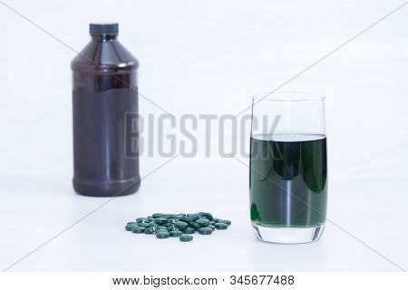 Chlorophyll In Glass Of Water, Green Pills, Bottle On White Wooden Background.