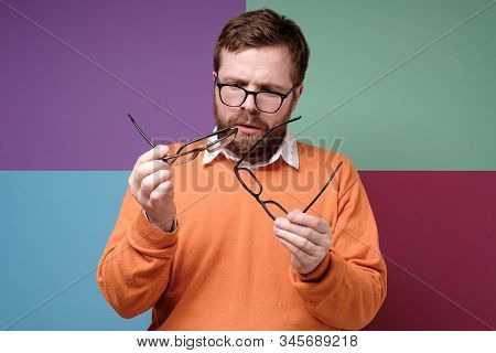 Bearded Man In Bewilderment And Stupor, He Selects And Compares Glasses, He Has To Solve A Difficult