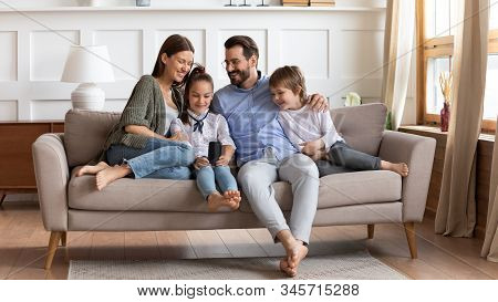 Happy Family With Kids Relax On Couch Using Cell