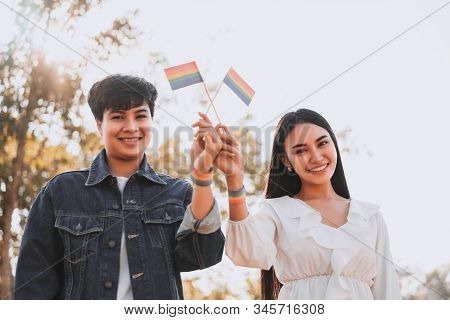 Young Women Lesbian Couple Holding A Lgbt Pride Flag . Lgbt Equal Rights Concept.