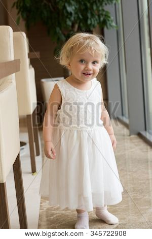 little girl in white dress indoors at home looking at camera