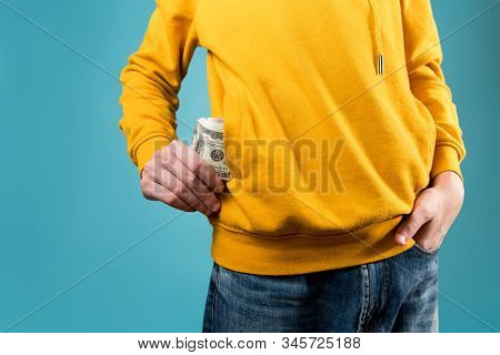Young Guy Takes Out Or Puts Money In A Pocket Of A Yellow Sweatshirt On A Blue Background