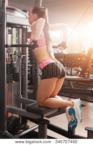 Athletic Girl Wearing Pink And Black Professional Sportswear Pulling Up At The Gym. Fitness And Work