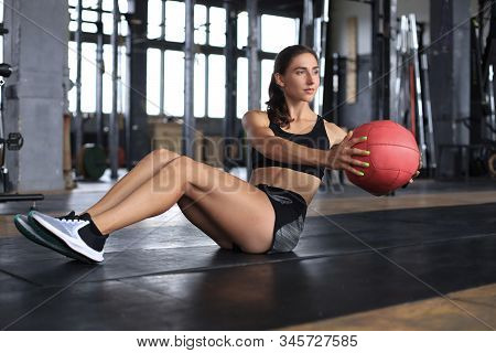 Fit And Muscular Woman Exercising With Medicine Ball At Gym.