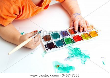 Baby Hands Hold A Brush And Watercolor Paints. Baby Art