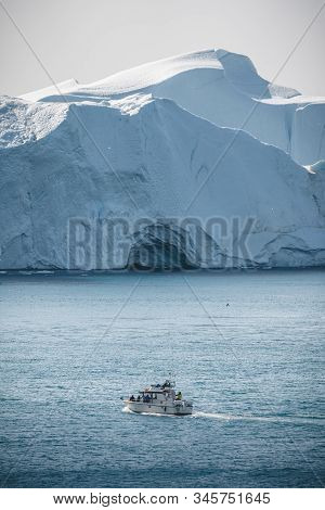 Passenger Cruise Ship Sailing Through The Icy Waters Of Arctic Landscape In Ilulissat, Greenland. A