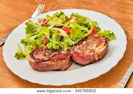 Tasty Pork Tenderloin Meat Steak In Dried Ham With Salad With Sloced Tomato And Cucumber On White Pl