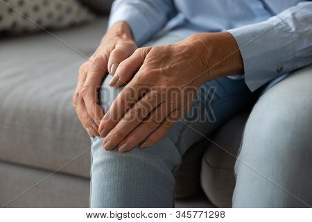 Close Up Older Woman Touching Knee With Hands, Feeling Pain