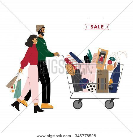 Happy Couple Are With Shopping Cart Full Of Purchases. Cute Man Is Carrying Cart, Smiling Woman Hold
