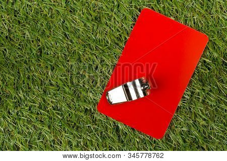 Soccer Sports Referee Red Card With Chrome Whistle On Grass Background - Penalty, Foul Or Sports Con