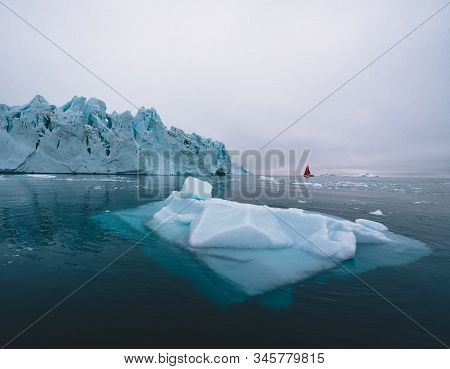 Beautiful Red Sailboat In The Arctic Next To A Massive Iceberg Showing The Scale. Cruising Among Flo