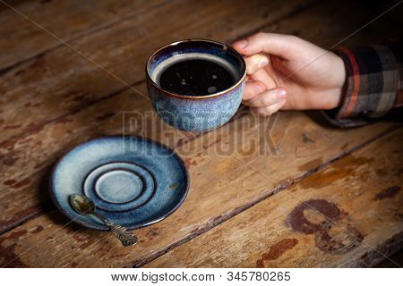 Closeup Black Americano Coffee In Blue Cup In Male Hand, Saucer With Vintage Tea Spoon On Background