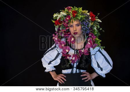 Young Woman In Black And White Folk Dress And Vivid Flower Crown